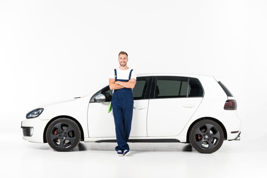 smiling handsome auto mechanic leaning on car with crossed arms on white