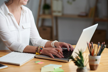 Cropped image of woman taking online class and writing down details