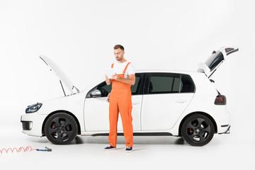 handsome auto mechanic using tablet near broken car on white