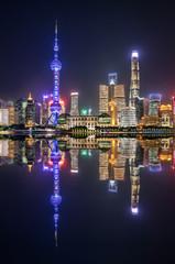 Blick auf die urbane Skyline von Shanghai bei Nacht mit Reflektionen im Huangpu Fluss, China