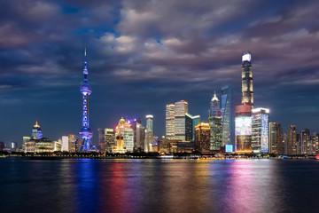 Die hell beleuchtete Skyline von Shanghai am Abend mit bewölktem Himmel, China