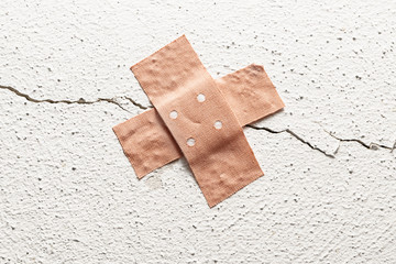 band-aid plaster in cross shape on a crack in the wall, concept for botched construction and doctoring around symptoms, copy space