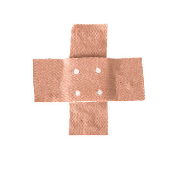 band-aid plaster in cross shape isolated on a white background, copy space