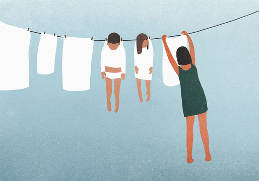 Woman hanging children on clothesline to dry