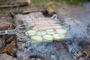 Photo of grill for barbecue with vegetables and sausages on fire in forest