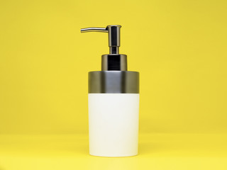 Blank white high quality hygiene liquid dispenser with metallic, reflective push hood, isolated on a yellow background