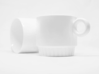 Two blank white mugs isolated on a white background