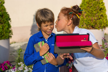 The girl kisses her younger brother and make a selfie on a tablet