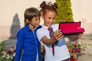 Children do selfie on the tablet and smile.