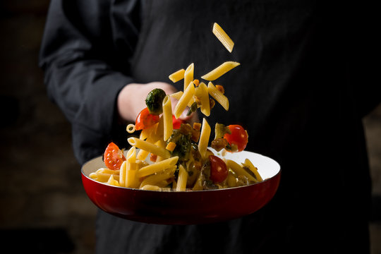 Cropped view of chef cooking Italian pasta with cheese, vegetables and egg yolk on hot pan flying.
