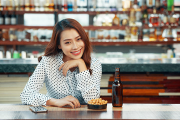 Cheerful attractive woman drinking beer and having snacks in pub