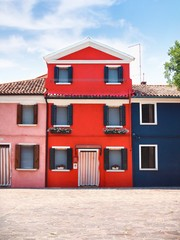 Street with colorful houses - red, blue, pink - in Venice, on the island of Burano, Hanging on the windows and drying clothes