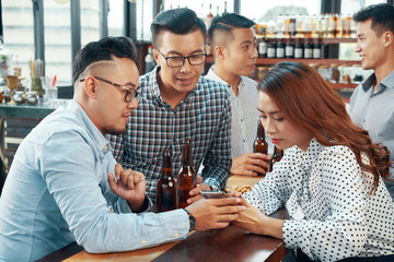 Colleagues discussing photo on smartphone when resting in pub after work