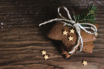 Christmas gingerbread cookies in star shape on wooden background. Christmas gift and beautiful decor.