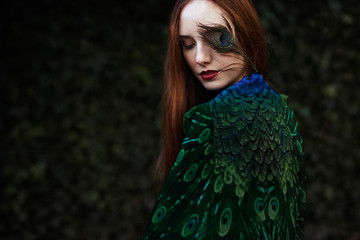 Young woman with peacock plumage