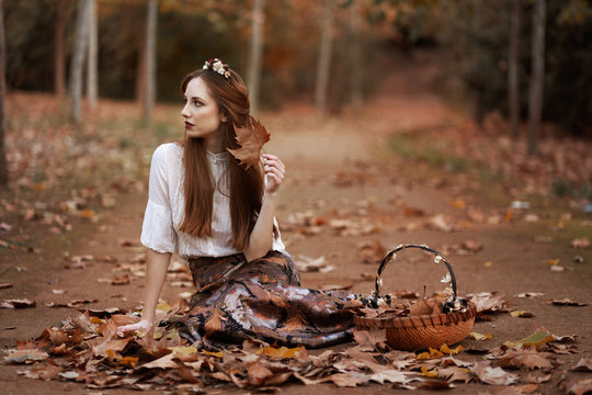 Lovely woman sitting on autumn leaves