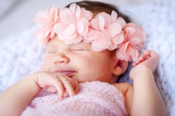 Cute sleeping newborn Caucasian baby girl a pink flower head bow. Sweet infant girl smiling in her sleep. A classical newborn infant photo session. First days of her life concept