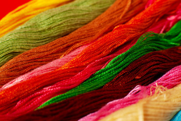 Many threads for embroidery. Macro. Multicolored threads for embroidery are folded in a row. Embroidery is a kind of needlework. Red, blue, green, yellow, orange thread.
