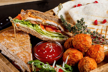 Sandwich with chicken, quesadilla with mushrooms, potato croquettes and fresh vegetable salad.