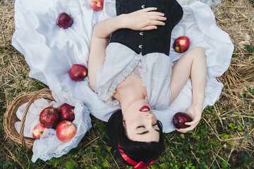 Snow White is laying in the floor, surrounded by red apples. She seems to be in a profound sleep. Fotomurales