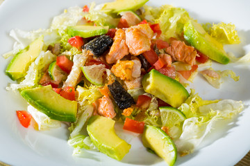 Closeup of salad with fried salmon, avocado, tomatoes and lettuce