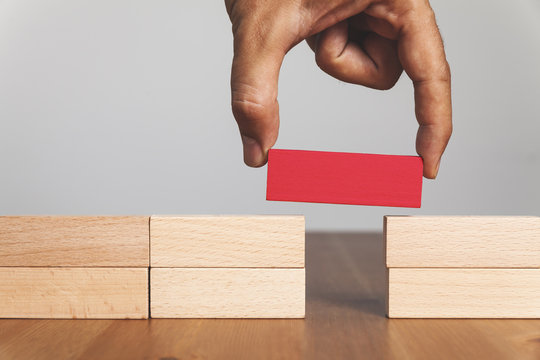 Man solving problems by building bridge with red wooden block