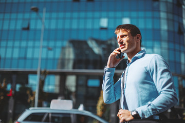 Modern businessman talking to the phone on the street