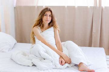 a portrait of a woman stretching in bed after wake up