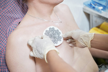 Tattoo artist putting stencil with beautiful drawing on chest of client