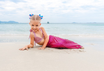 Little beautiful girl dressed in swimsuit as a mermaid sits on the seashore