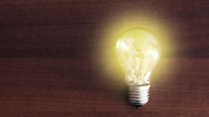 Bulb on wooden table, concept of idea