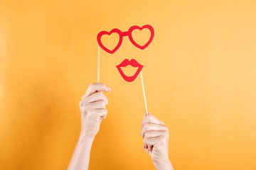 Close up of young woman hands holding carnival accessories, lips and glasses in heart shape on stick made from red paper. Female with funny party attributes. Yellow wall background, copy space.