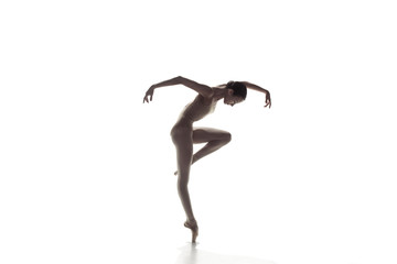 Young graceful female ballet dancer or classic ballerina dancing isolated on white studio....