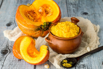 Clay pot with millet porridge and a ripe fresh pumpkin on a napkin on an old wooden table.