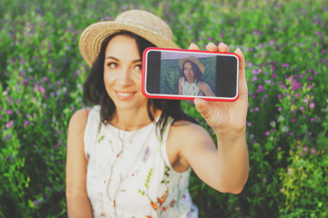 Beautiful young woman taking a selfie on the field of clover