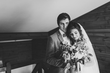 The groom in suit hugs bride in white dress are holding a beautiful wedding bouquet flowers, greenery and decorated with ribbon at home. Portrait of a beautiful young couple. Black and white photo.