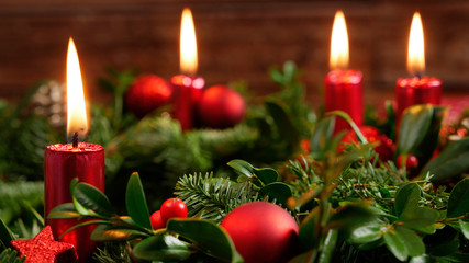 Decorative advent wreath of green fir twigs and mistletoes with red candlelight and shiny baubles...