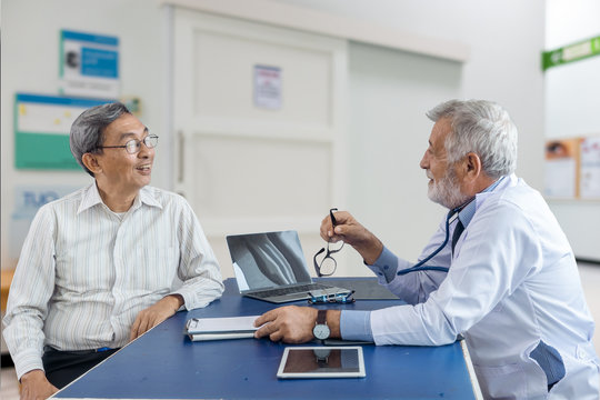 The elderly patient man talking with senior doctor