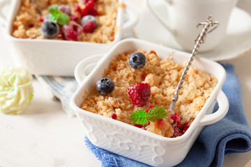 Traditional British apple crumble on portion baking dish with fresh berries