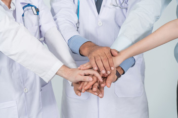 Close up doctor and nurse in a medical team stacking hands