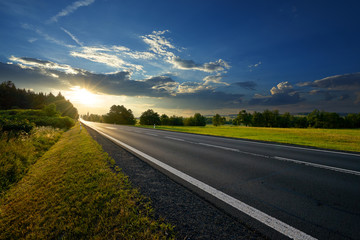 Fotobehang - Empty asphalt road in the countryside at sunset