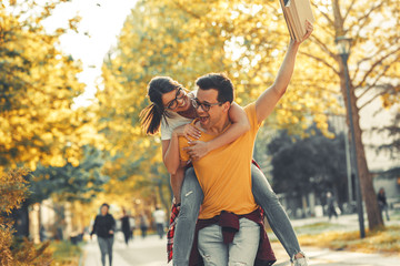Young student couple making fun at the campus yard.man carrying his girlfriend on his back.Autumn.