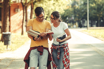 Young student couple going to college class.They walks trough university campus and reading a book.Autumn season.