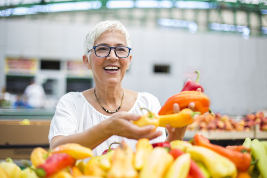 Good-looking senior woman wearing glasses buys pepper on market