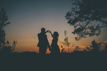 loving couple in silhouette on the sunset