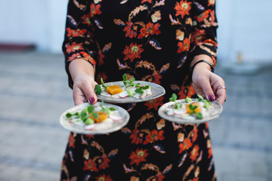 Fresh ceviche starter carried by waitress in bold floral dress