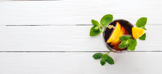 Alcoholic cocktail of whiskey, lemon and mint. Rum-Cola. Brandy. On a white wooden background. Free space for text.