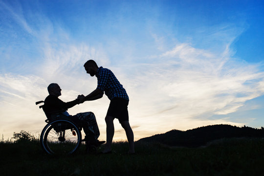 A silhouette of adult son looking at his father in wheelchair in nature at sunset.