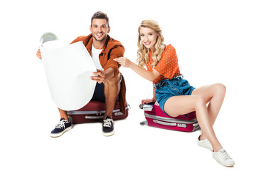 smiling couple sitting on travel bags with map isolated on white