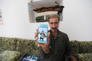 Ibrahim Jenbod, shows his 20-year-old son's picture on a cell phone in the city of al-Bab